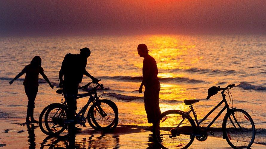 zdjęcie przestawia rowerzystów na plaży